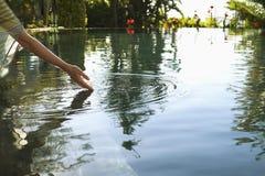 Woman Touching Water Of Swimming Pool Stock Photo