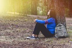 Woman tourism. Back of traveler in the forest. Beautiful young woman is traveling and resting in the forest. royalty free stock photography