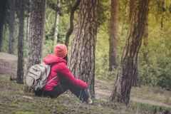 Woman tourism. Back of traveler in the forest looks for the road. Beautiful young woman is traveling and resting in the forest stock photos