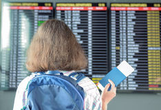 Woman tourist in airport terminal waiting for flight and looking at timetable with passport and ticket. Travel concept Royalty Free Stock Photos