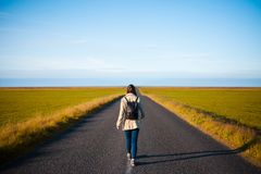 Woman tourist with backpack on the background road. Toward the goal Stock Photos