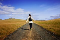 Woman tourist with backpack on the background road. Toward the goal Royalty Free Stock Image