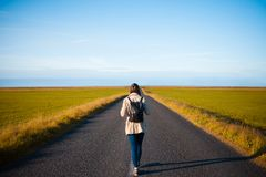 Woman tourist with backpack on the background road. Toward the goal Royalty Free Stock Photo