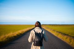 Woman tourist with backpack on the background road. Toward the goal Stock Photo