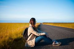 Young woman tourist sits on the road. Royalty Free Stock Images