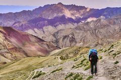 Woman tourist with a backpack climbing steep slope with beautiful colorful Himalaya mountains in the background, Ladakh, India stock photos