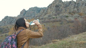Woman tourist with backpack drinking water in stock video