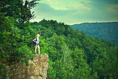 Woman tourist with a backpack on a mountain top on a rock on the. Nature of the journey Royalty Free Stock Photography