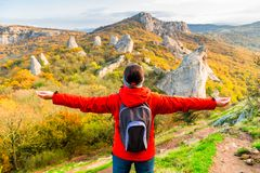 Woman Tourist with a backpack with open arms enjoying the autumn landscape stock photos