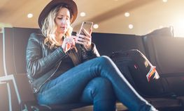 Woman tourist with backpack sits at airport, uses smartphone. Hipster girl is waiting for plane landing,checks email. Young woman tourist in hat, with backpack Stock Images