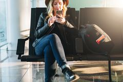 Woman tourist with backpack sits at airport, uses smartphone. Hipster girl is waiting for plane landing,checks email. Young woman tourist in hat, with backpack Royalty Free Stock Photography