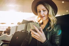 Woman tourist with backpack sits at airport, uses smartphone. Hipster girl is waiting for plane landing,checks email. Young woman tourist in hat, with backpack Royalty Free Stock Photo