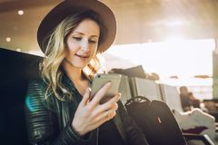 Woman tourist with backpack sits at airport, uses smartphone. Hipster girl is waiting for plane landing,checks email. Young woman tourist in hat, with backpack Stock Photography