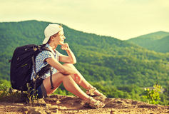 Woman tourist with a backpack sitting, resting on a mountain top. On a rock on the nature of the journey Stock Photos