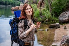 Woman tourist with a backpack walk in a hike against a background of beautiful mountain scenery along a mountain river royalty free stock photography