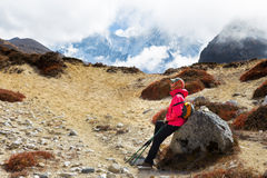 Woman tourist backpacker resting rock Ama Dablam mountain trail. Royalty Free Stock Photography