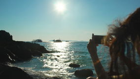 Woman tourist on beach island taking photograph of sunset with smartphone on holiday of boat and skyline view stock footage