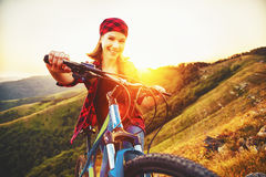 Woman tourist on a bicycle at top of mountain at sunset outdoors Stock Images