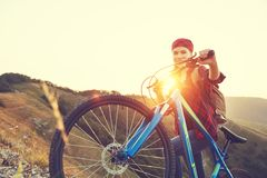 Woman tourist on a bicycle at top of mountain at sunset outdoors Stock Photos