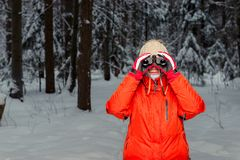 Woman tourist with binoculars in the winter. Forest Royalty Free Stock Photography