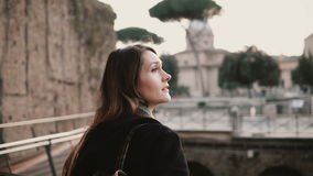 Woman tourist in black coat is walking across the bridge in Roman Forum. Girl excited about ancient city of Rome, Italy. stock footage