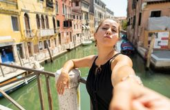 Woman tourist blowing a kiss while taking a selfie at the canal in Venice Italy royalty free stock photos
