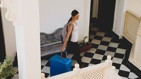 Young woman with suitcase check-in to the hotel. stock photo