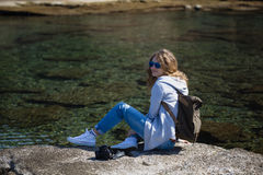 Woman tourist with camera and backpack sitting and relaxing. Blond woman tourist wearing sunglasses khaki backpack gray jacket and jeans sitting and relaxing on Stock Photography