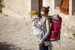 Woman tourist carrying her little son in sling Stock Images