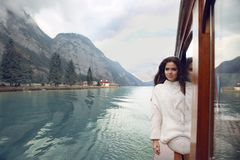 Woman tourist in cozy sweater enjoying on boat in Konigssee lake. Berchtesgaden, Germany. Young brunette traveler in warm white clothes style enjoying and Royalty Free Stock Photo