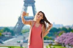 Woman tourist at Eiffel Tower making travel selfie. Woman tourist at Eiffel Tower smiling and making travel selfie. Beautiful European girl enjoying vacation in Royalty Free Stock Photography