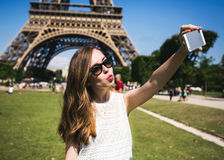 Woman tourist at Eiffel Tower smiling and making. Woman tourist at Eiffel Tower smiling making travel selfie. Beautiful European girl enjoying vacation in Paris Royalty Free Stock Images