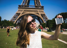 Woman tourist at Eiffel Tower smiling and making. Woman tourist at Eiffel Tower smiling making travel selfie. Beautiful European girl enjoying vacation in Paris Royalty Free Stock Photography