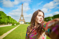 Woman tourist at Eiffel Tower smiling and making travel selfie Stock Photos