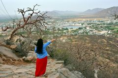 Woman tourist enjoying bird eye view of Pushkar lake or Pushkar Sarovar at Pushkar - Rajasthan - India Stock Photos