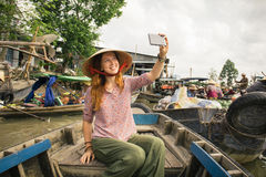 Woman tourist on floating market in Vietnam. Woman tourist take selfie photo from the boat on Cai Rang floating market, Can Tho, Vietnam Stock Images