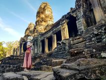 Woman tourist in Bayon temple in Angkor Wat. Woman tourist in front of Bayon temple in Angkor Wat stock image