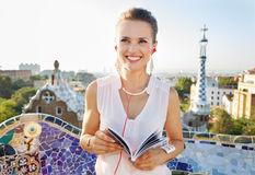 Woman with tourist guide listening audioguide in Park Guell Royalty Free Stock Photography