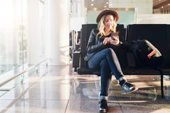 Woman tourist in hat, with backpack sits at airport near window, uses smartphone. Hipster girl waiting for plane landing royalty free stock images