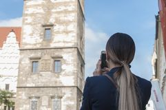 Woman tourist with her phone camera in hands shooting in Prague. Under sunlight and blue sky in sunny day. One of popular touristic place in Prague Royalty Free Stock Photo