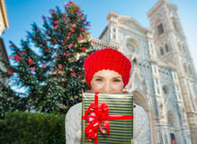 Woman tourist hiding behind christmas gift box in Florence. Cheerful woman tourist in winter outfit hiding behind present gift box while standing near large Royalty Free Stock Photo