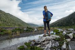 Woman tourist hiker. Stands near the river and observs the valley, Chile royalty free stock image