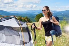 Woman tourist hiking in mountain trail, enjoying summer sunny morning in mountains near tent. Beautiful happy woman hiker hiking mountain trail, standing near royalty free stock images