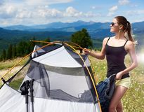 Woman tourist hiking in mountain trail, enjoying summer sunny morning in mountains near tent. Beautiful happy woman tourist hiking in Carpathian mountain trail royalty free stock images