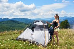 Woman tourist hiking in mountain trail, enjoying summer sunny morning in mountains near tent. Pretty smiling woman hiker hiking mountain trail, standing near stock photography