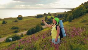Woman tourist on a hill with a backpack behind him and binoculars makes a photo on the phone. The average plan stock video footage