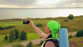 Woman tourist on a hill with a backpack behind him and binoculars makes a photo on the phone. Close-up stock video
