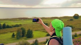 Woman tourist on a hill with a backpack behind him and binoculars makes a photo on the phone. Close-up stock footage