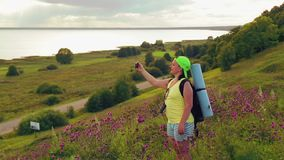 Woman tourist on a hill with a backpack behind him and binoculars makes a photo on the phone. The average plan stock footage