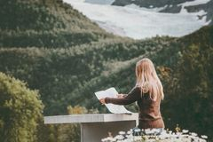 Woman tourist holding map planning route trip in Norway sitting at the table Travel Lifestyle Stock Image